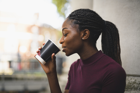 Woman with braids having a cup of hot coffee Stock Photo
