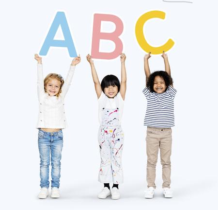 Diversos niños felices aprendiendo el ABC