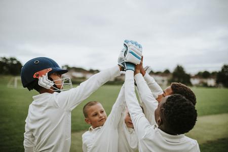 Gruppe junger Cricketspieler, die ein High Five machen Standard-Bild