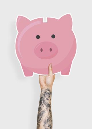 Hand holding a piggy bank cardboard prop Stock Photo