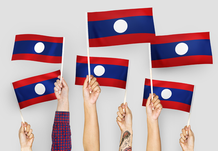 Hands waving flags of Lao PDR 스톡 콘텐츠