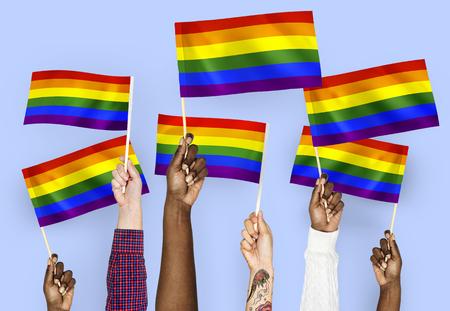 手挥舞着彩虹旗帜