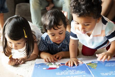 Niños leyendo un libro en el suelo.