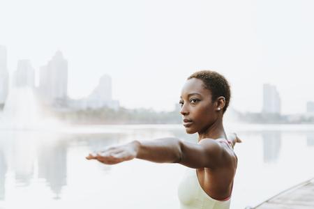 Black lady doing a virabhadrasana pose
