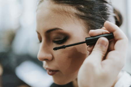 Makeup artist applying mascara onto the model
