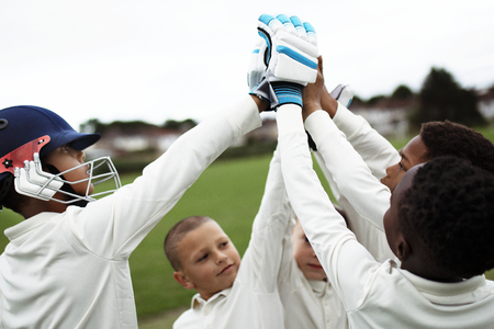 Group of young cricketers doing a high five Imagens