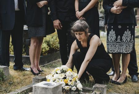 Family laying flowers on the grave Zdjęcie Seryjne - 116690388