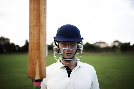 Cricket player holding a bat on the field Banco de Imagens