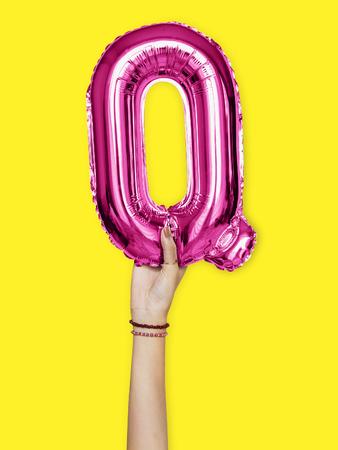 Hand holding balloon letter Q