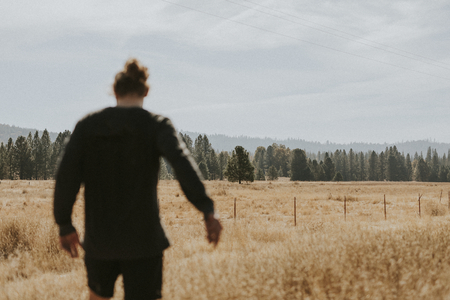 Rear view of a man walking in the countryside Banco de Imagens