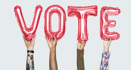 Hands holding vote word in balloon letters Stockfoto
