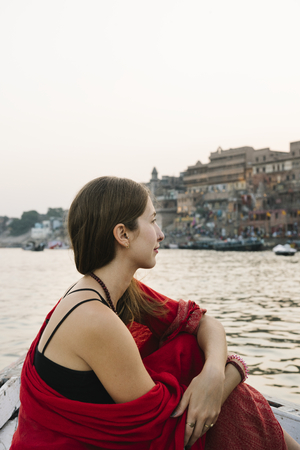 Western woman on a boat exploring the River Ganges Stock Photo