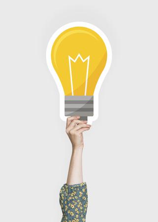 Hand holding a light bulb cardboard prop
