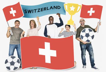 Diverse football fans holding the flag of Switzerland Foto de archivo