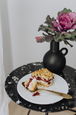 Slice of cheesecake next to an ornamental kale on a black table