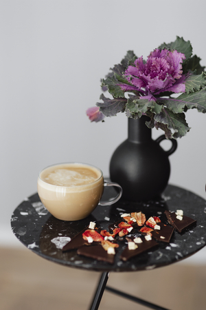 Dark chocolate brittle and milk tea on a black table with an ornamental kale flower Stock Photo - 116606376