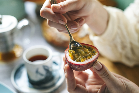 Woman scooping out the insides of a passion fruit Stock Photo
