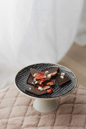 Dark chocolate brittle on a plate on top of a pink velvet cushion