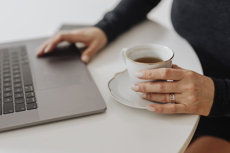 Woman with a cup of tea and a laptop