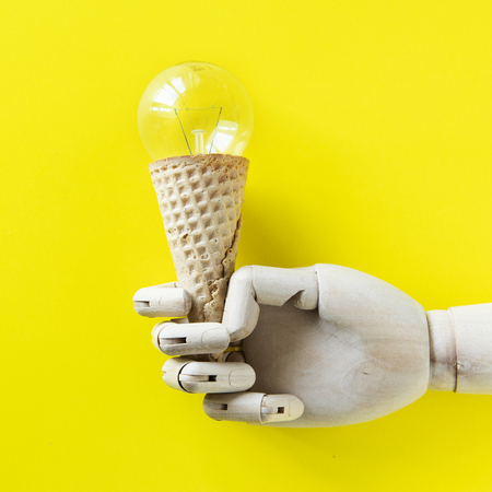 Robot hand holding a light bulb ice cream Banque d'images - 116609022