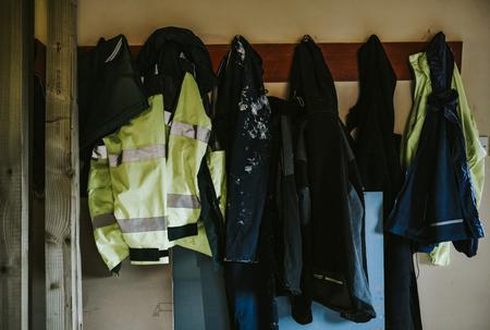 Arbeitskleidungsmäntel und -jacken hängen an einem Gestell