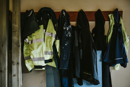 Workwear coats and jackets hanging on a rack 写真素材