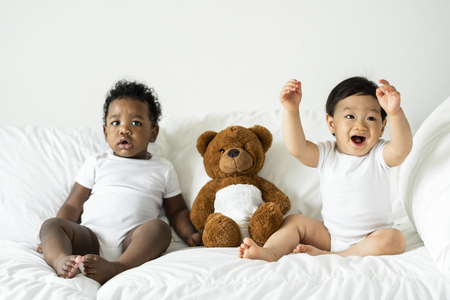 Babies and a teddy bear on the bed Stock Photo