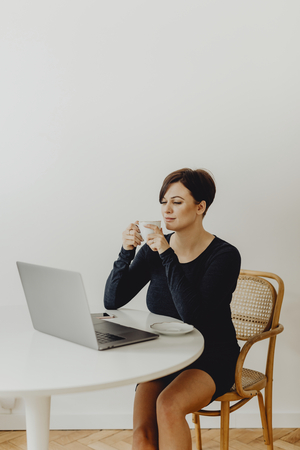 Positive woman with a cup of tea telecommuting Stock Photo - 116615022
