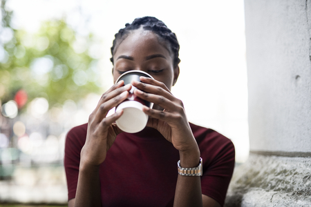 Woman drinking coffee out of a paper cup 스톡 콘텐츠