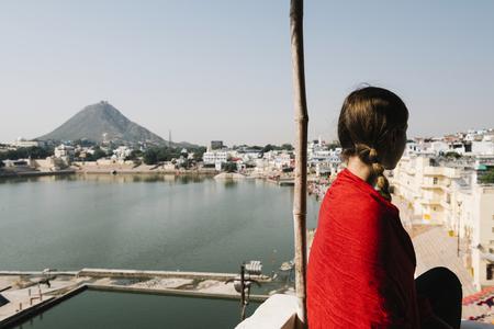 Western woman enjoying a view of Pushkar lake in Rajasthan