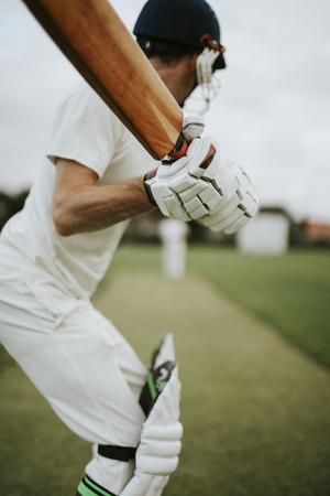 Cricketer on the field in action Stock Photo