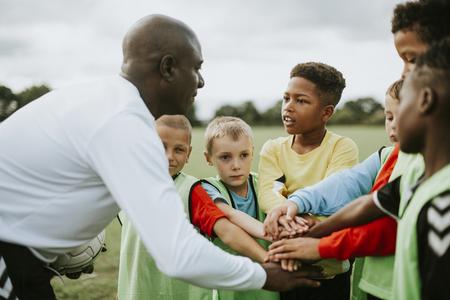 Junior voetbalteam handen stapelen voor een wedstrijd