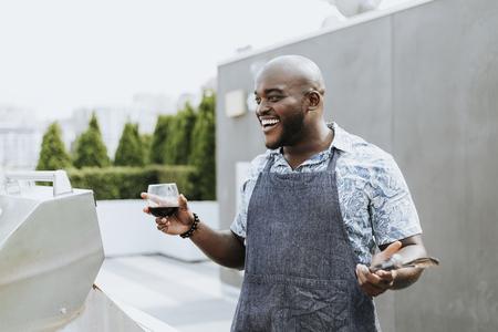 Chef allegro con pinze per grigliare e un bicchiere di vino