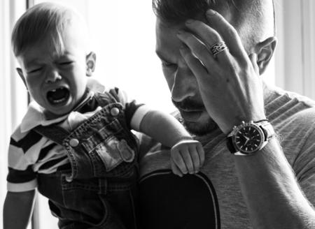 Padre estresado sosteniendo a un bebé llorando Foto de archivo