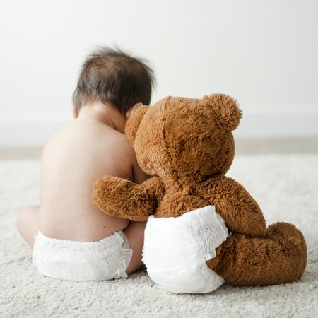 Dos d'un bébé avec un ours en peluche Banque d'images