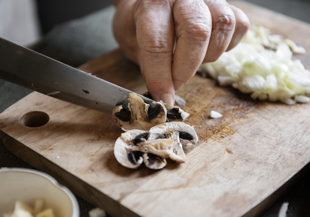 Man cutting mushrooms on a wooden board