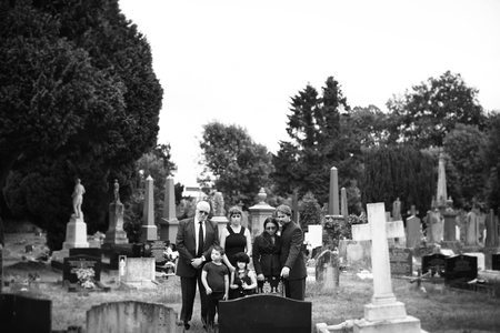 Sad family standing at a cemetery Stock Photo