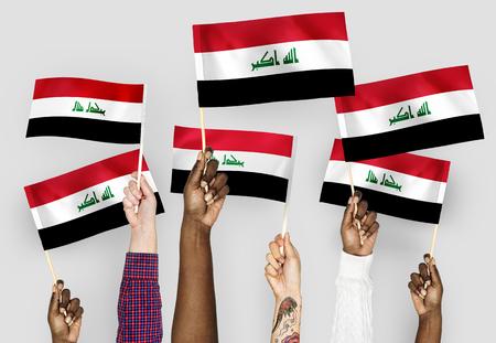 Hands waving flags of Iraq