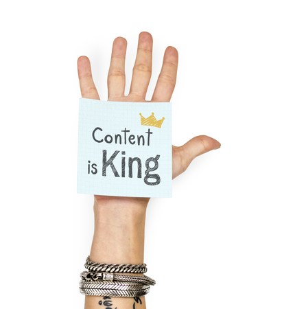 Hand showing a sticky note with Content is king