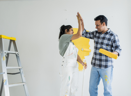 Couple giving a high five while renovating their new house Standard-Bild - 116618705