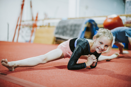 Young gymnast stretching her body 免版税图像
