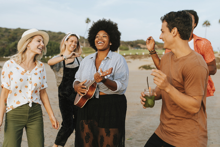 Friends singing and dancing at the beach Stock Photo
