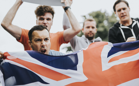 Group of angry men showing a UK flag and blank boards shouting during a protest Stockfoto - 116618954