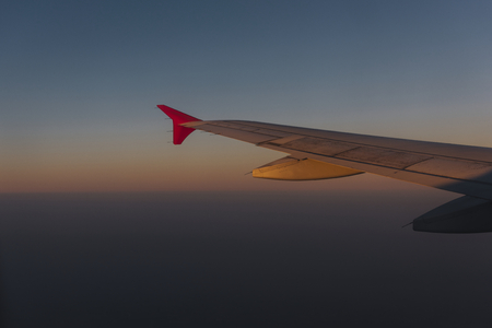 Wing of a plane flying in a dusky sky