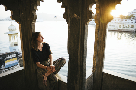 Western woman sitting on a cultural architecture in Udaipur, India