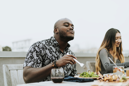 Man enjoying a fresh vegan salad at a rooftop party