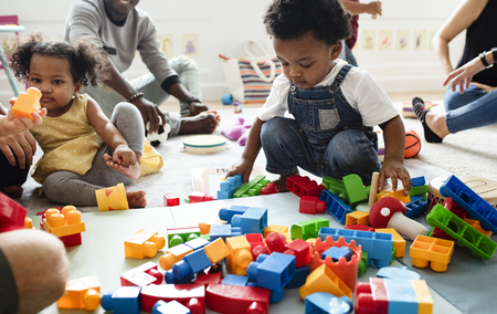 Diverse children enjoying playing with toys Standard-Bild