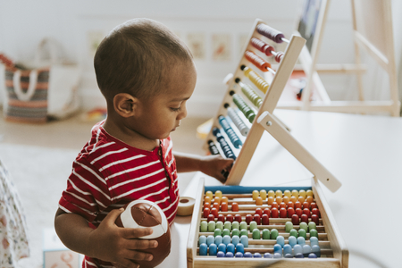 Kid playing with a colorful wooden abacus Foto de archivo