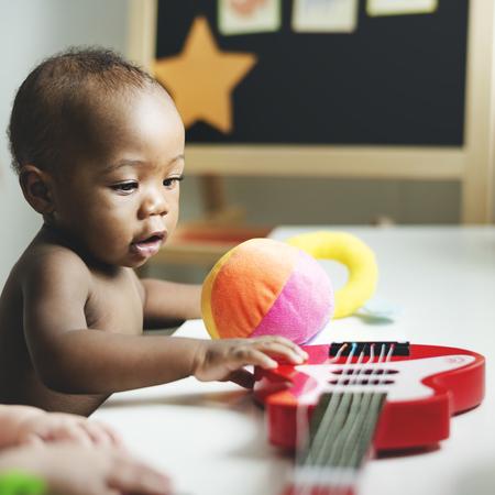 Il bambino gioca con una chitarra giocattolo