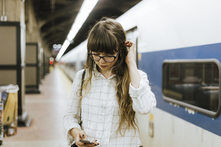Thoughtful woman listing to music while waiting for a train at a subway platform Stock Photo
